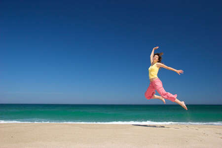 beautiful woman jumping in the beach photo