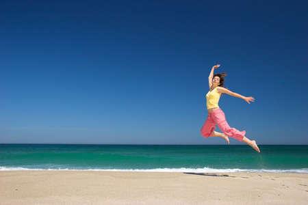 beautiful woman jumping in the beach photo