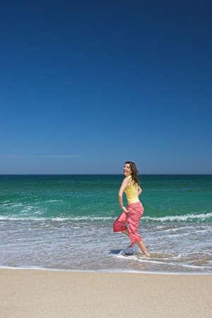 Happy woman running in the beach photo