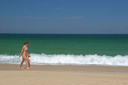 Beautiful young womens walking in the beach photo