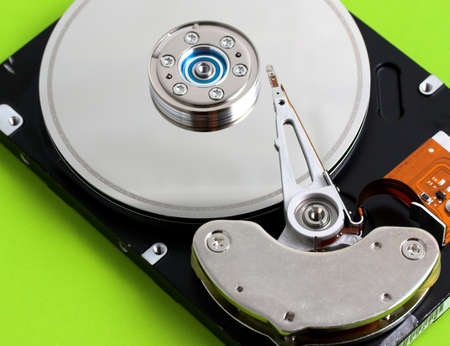 Open hard disk drive in a green background photo
