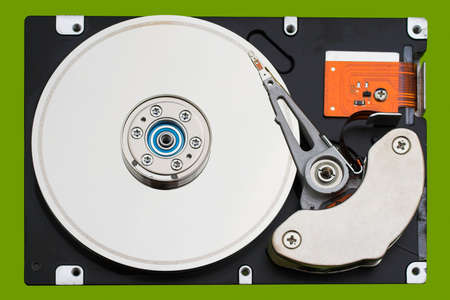 Open hard disk drive, in a green background photo