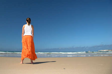Beautiful woman in the beach with a orange skirt photo