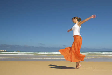 Beautiful woman dancing in the beach photo