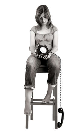 Sad woman seated in a chair with a the phone on is hands photo