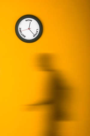 stated: Clock in the orange wall with a man in motion blur