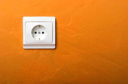 Electric wall plug at a orange wall Stock Photo - 567459