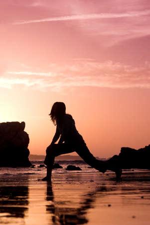 haciendo ejercicio: Mujer que hace ejercicio en la playa