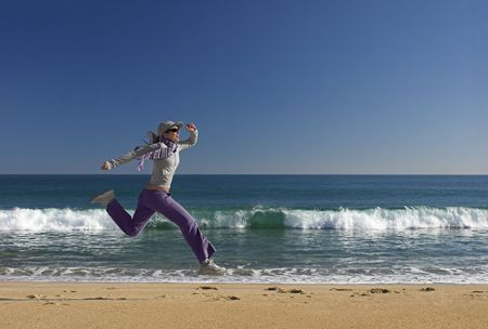 Young woman jumping for fun in a beautiful beach photo
