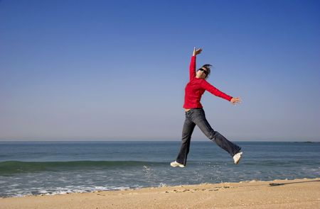 Young woman jumping for fun in a beautiful beach Stock Photo - 836622