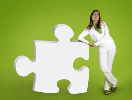 Woman contemplating questions with 3D puzzle form on a green background