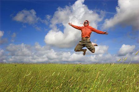 El hombre saltando sobre un prado verde con un hermoso cielo nublado