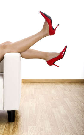 Woman legs in a sofa with red stylish shoes Stock Photo - 2086866
