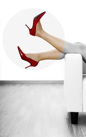 ankles sexy: Woman legs in a sofa with red stylish shoes (partiality desaturated in PS)   Stock Photo