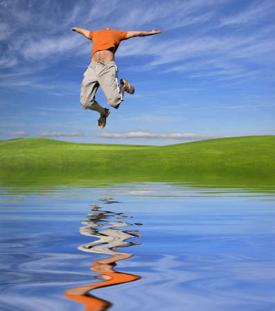 ps: Jump to the sky over a flowery field (reflection made in PS) Stock Photo