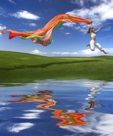 Young beautiful woman jumping with a scarf (reflection made in PS) photo