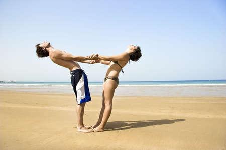 position d amour: En couple de jeunes gens s'amusent sur la plage Banque d'images