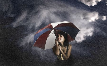 Portrait of a young happy woman posing with a umbrella under rain Stock Photo - 2422236