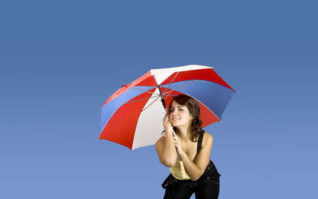 Portrait of a young happy woman posing with an umbrella on a blue background Stock Photo - 2510720