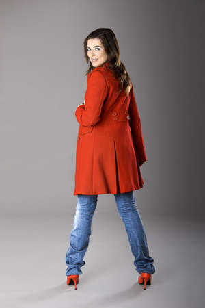 Beautiful fashion woman posing with a red coat photo