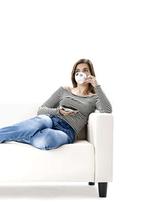 Beautiful woman relaxing on a white sofa with a cup of coffee Stock Photo - 2676048