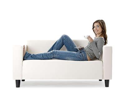 relaxing: Beautiful woman relaxing on a white sofa with a cup of coffee Stock Photo