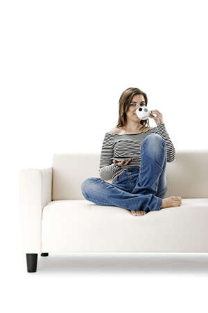Beautiful woman relaxing on a white sofa with a cup of coffee Stock Photo - 2676045