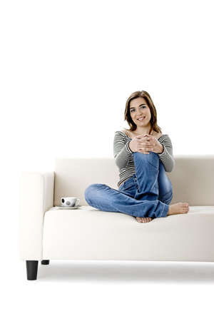 Beautiful woman relaxing on a white sofa with a cup of coffee photo