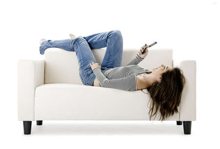 Beautiful happy woman on a white sofa making a phone call photo