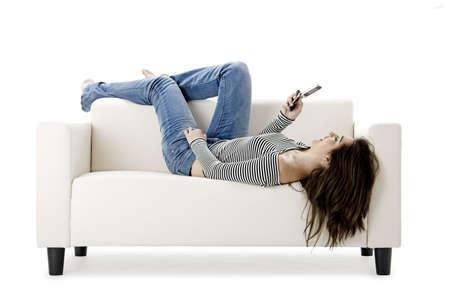 Beautiful happy woman on a white sofa making a phone call