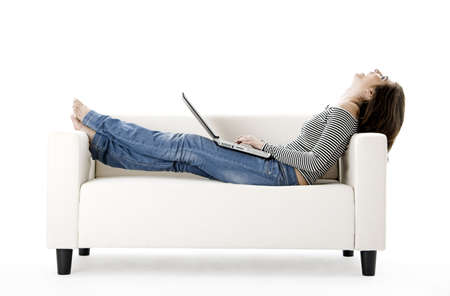 Beautiful woman on a white sofa with a laptop