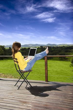 Woman enjoying a beautiful day with a laptop on her home-field photo