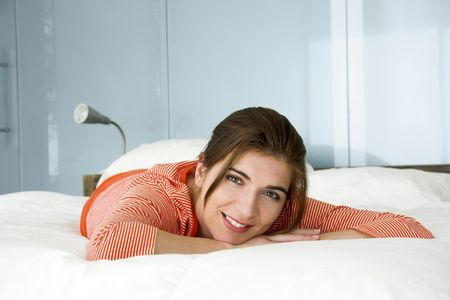 Portrait of a beautiful woman in bed smiling photo