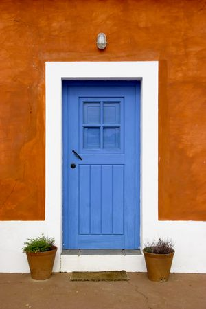 Beautiful and funny orange house with blue doors and windows Stock Photo
