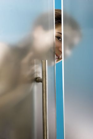 Beautiful and happy woman looking and closing the bathroom door photo