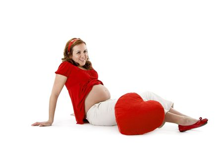 Beautiful pregnant woman enjoying this wonderful moment with a red Heart photo