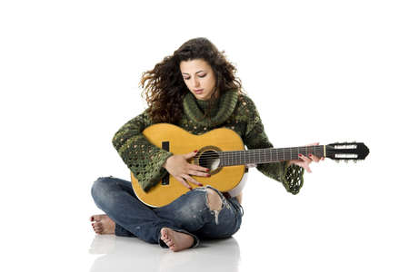 Beautiful woman isolated on white playing music with a guitar photo