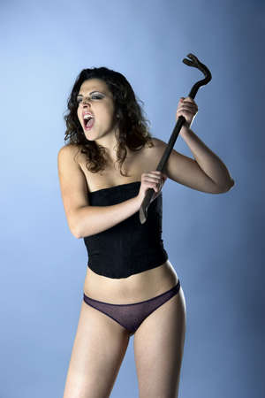 Angry sexy woman in lingerie posing with a metal tool photo