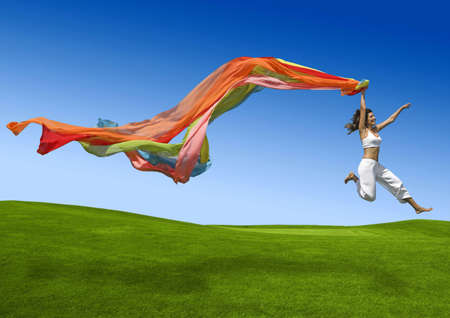 Athletic woman jumping on a green meadow  Фото со стока
