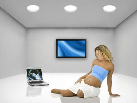 Beautiful pregnant woman seated on the floor inside a room with a laptop and tv  photo