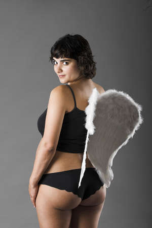 Studio portrait of a beautiful pregnant woman with angel wings photo