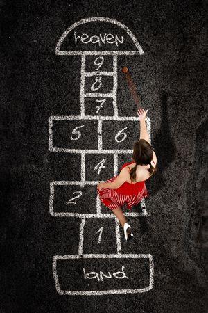 Mooie jonge vrouw spelen Hinkelspel met een rode jurk