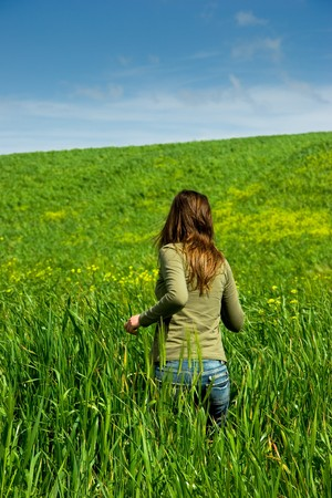 Woman runing to inside of a green harvest field photo