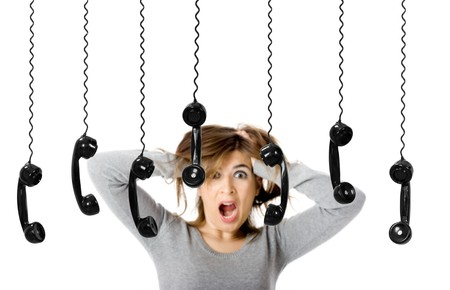 Beautiful woman in shock looking to a lot of telephones photo