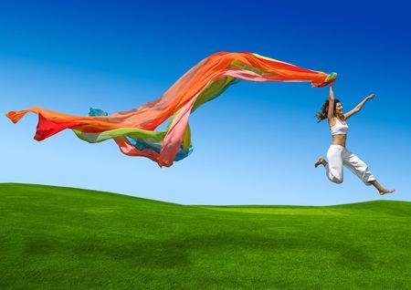Giovane bella donna che salta con una sciarpa Archivio Fotografico