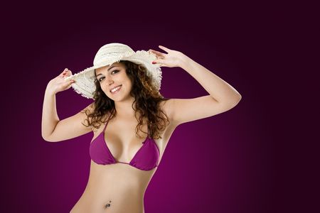 Portrait of a beautiful young woman in bikini posing on a violet background photo