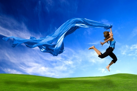 Beautiful athletic woman jumping on a green meadow with a scarf Фото со стока