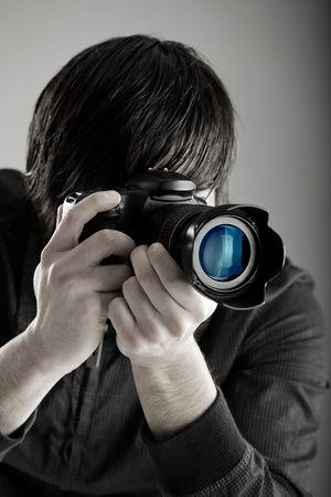Young man holding a professional DSLR camera and taking pictures Stock Photo