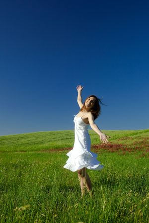 Beautiful happy young woman dancing on the field  photo
