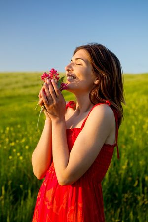 Beautiful happy woman on the field holding flowers photo